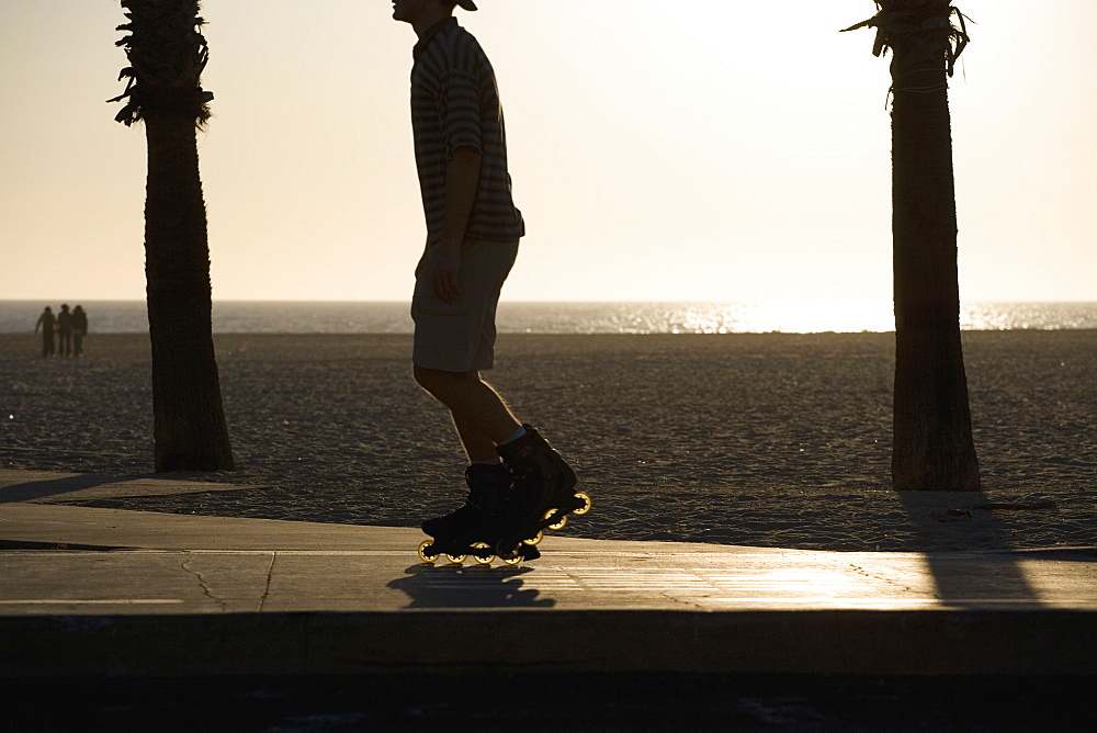 A rollerblader at the beach at sunset