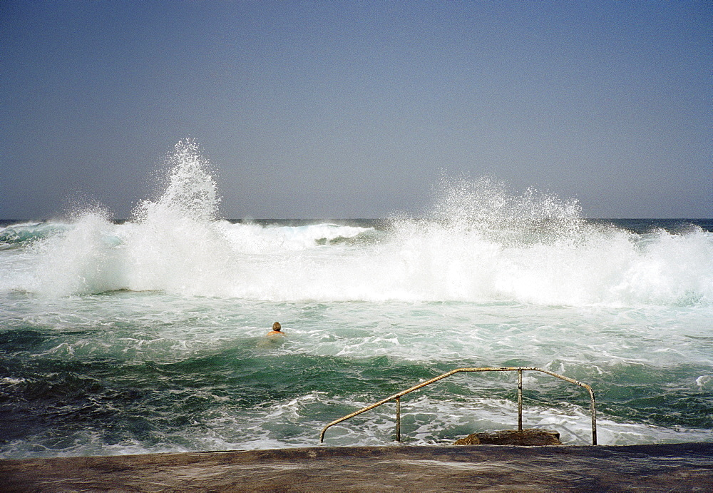 A person swimming into crashing waves