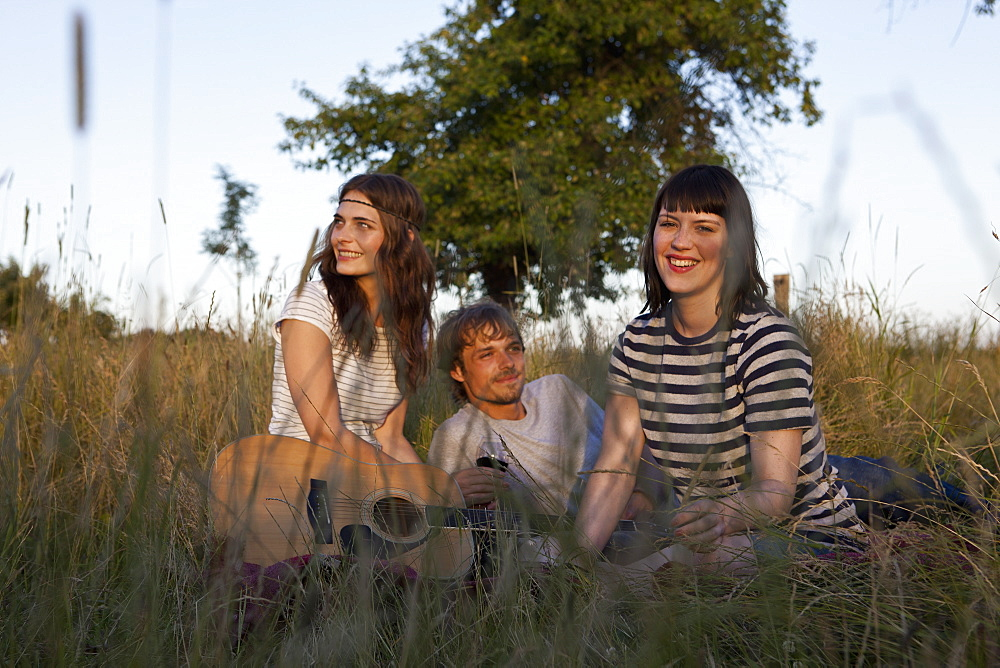 Three friends amongst the timothy grass with wine and guitar