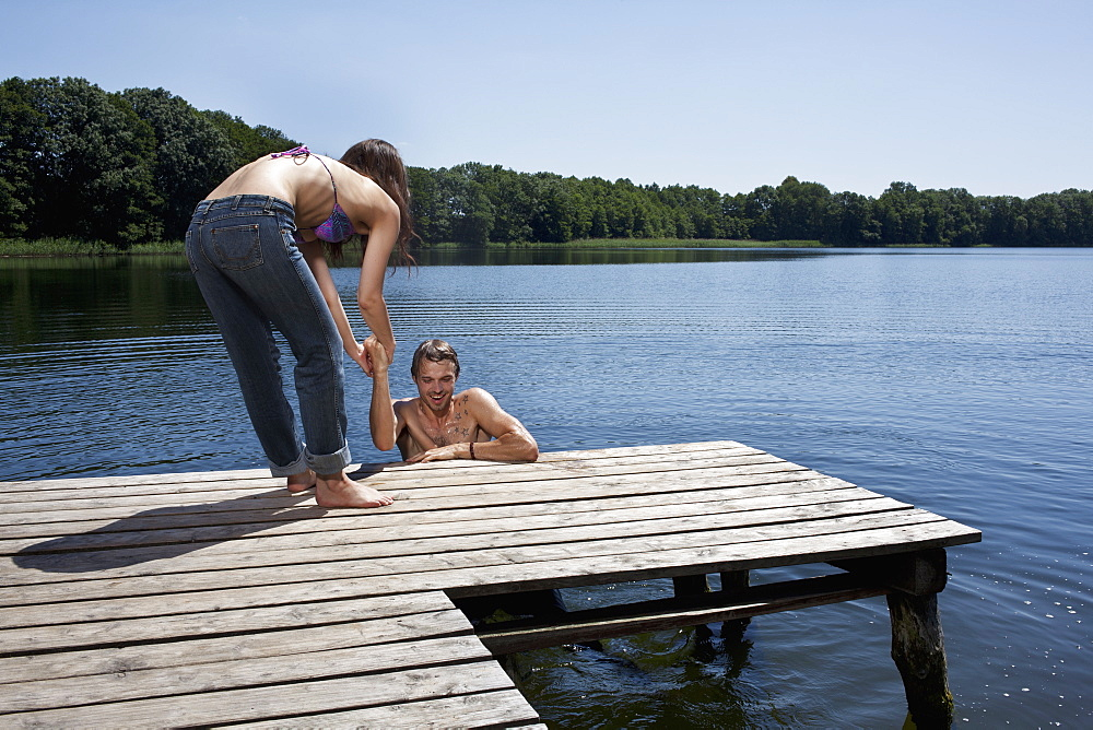 Fun as woman helps man out of the water on jetty