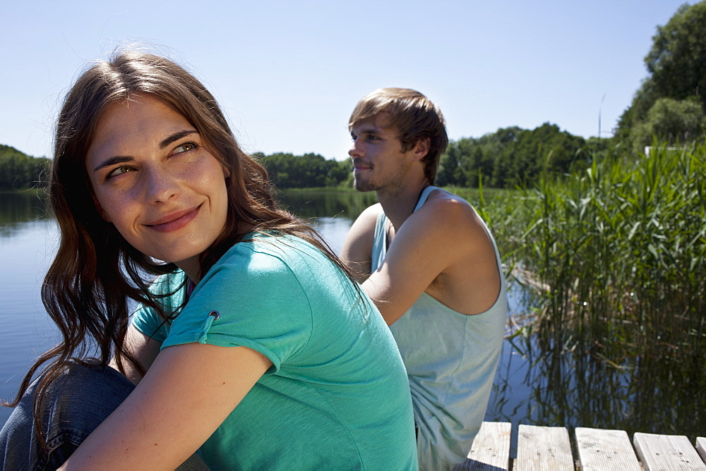 Couple side by side on jetty with girl looking very happy