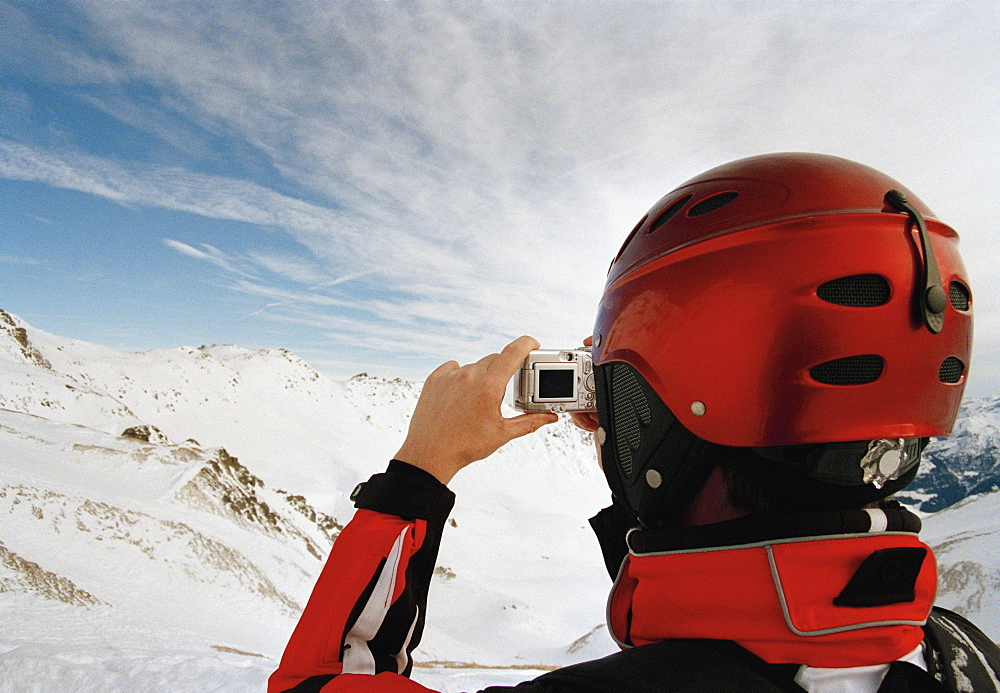 A skiier taking a photograph of the austrian alps