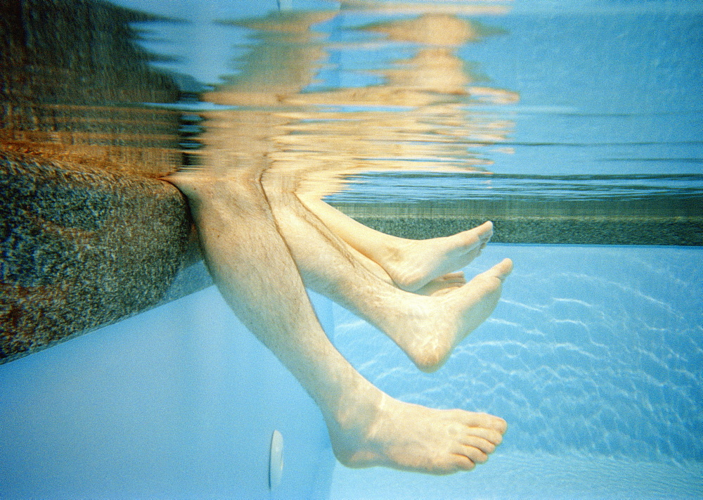 Four human legs underwater in a swimming pool
