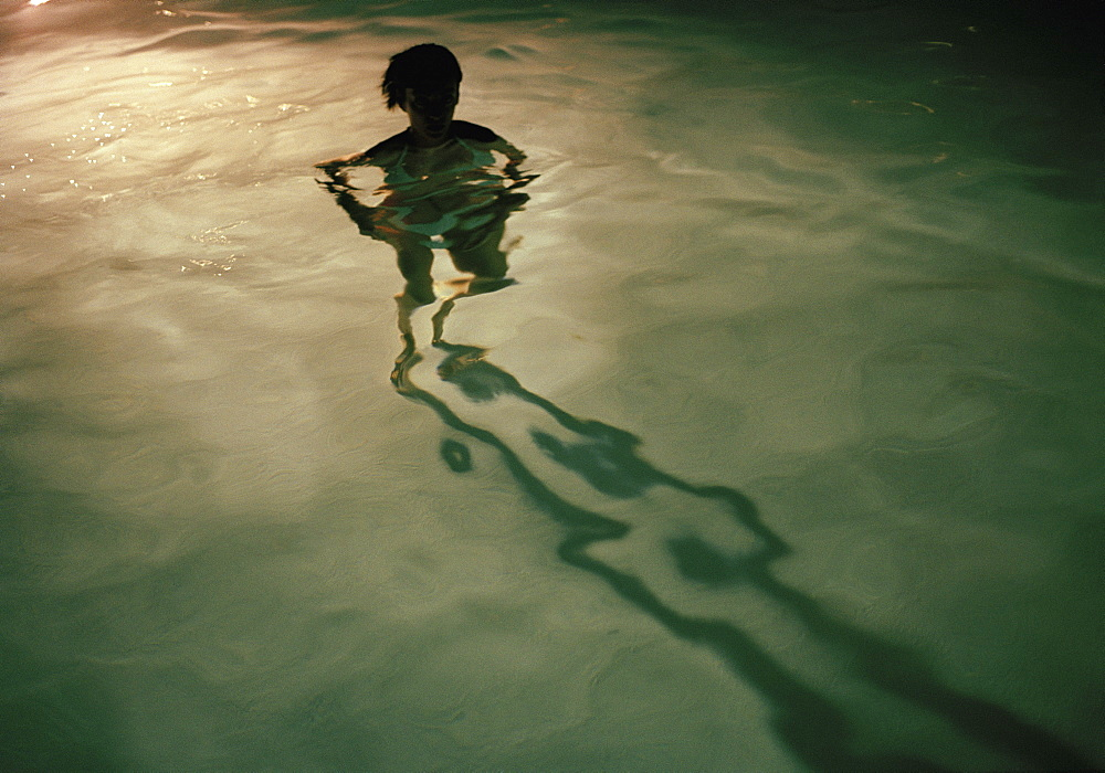 A young woman standing in a swimming pool at night, silhouette