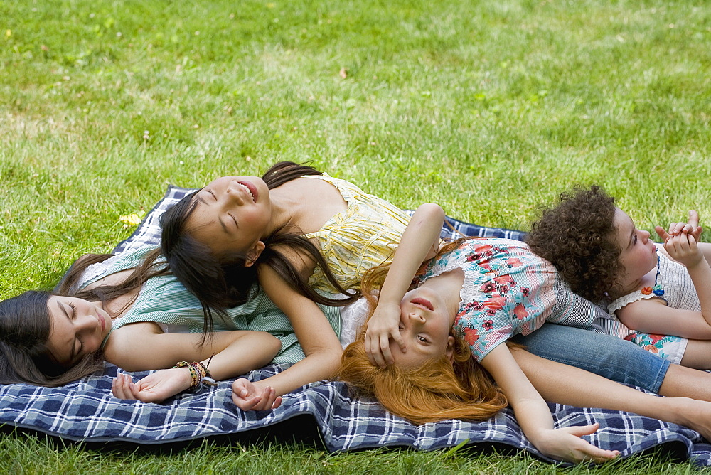 Four girls lying on top of each other