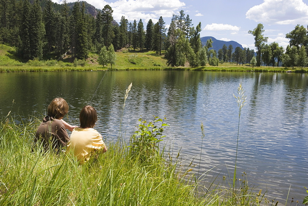 Two boys fishing at the edge of a lake, durango, colorado, usa