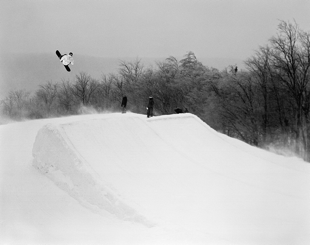 A snowboarder going over a jump, stratton, vermont, usa