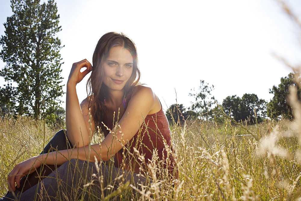 Girl sitting amongst timothy grass in the sunshine playing with her hair