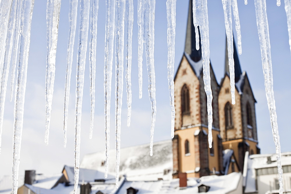 Detail of icicles and a church in the background
