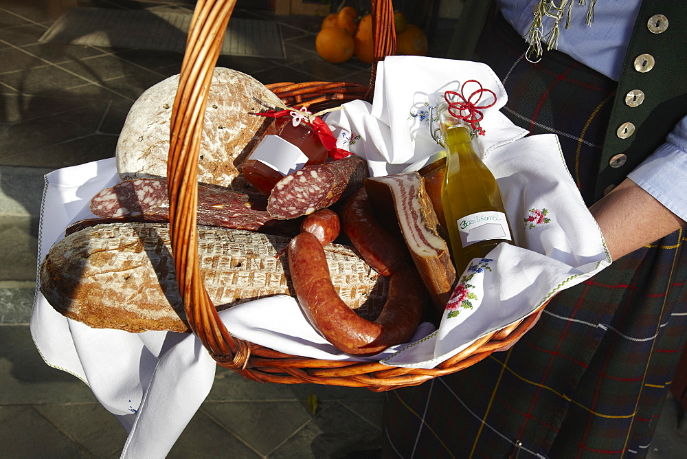 A woman holding a basket of sausages and bread, focus on basket, carinthia, austria