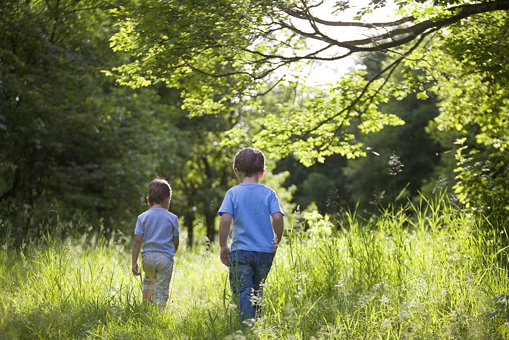 Two young boys walking outdoors in summer
