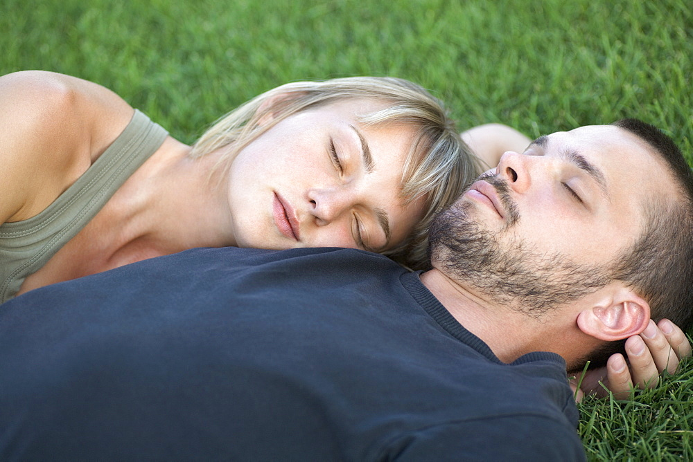 Man and woman sleeping on grass