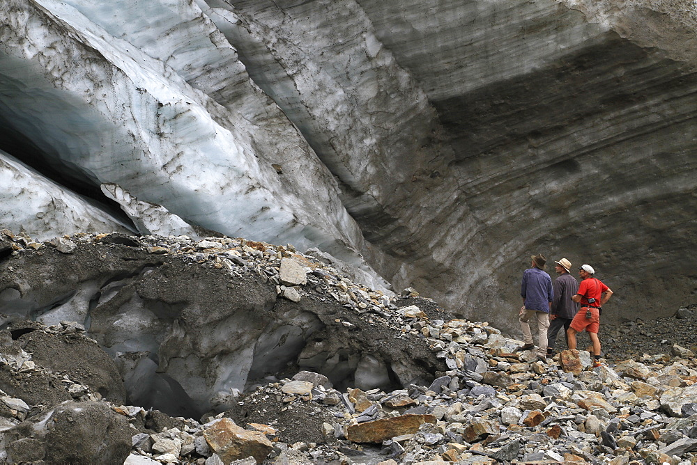 Three men standing at the foot of a glacier