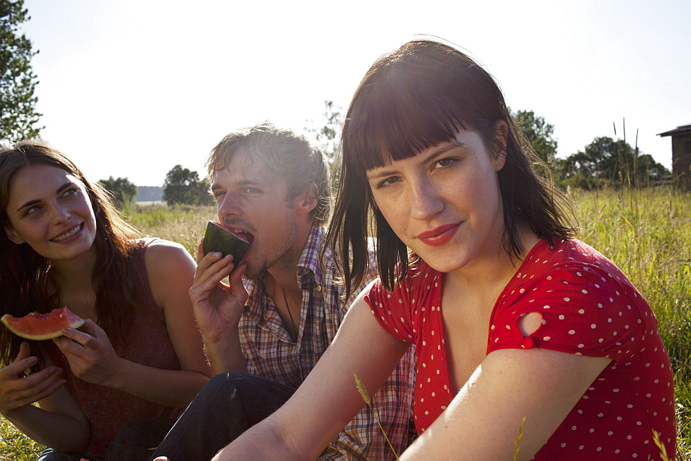 Three people side by side in a field eating melon