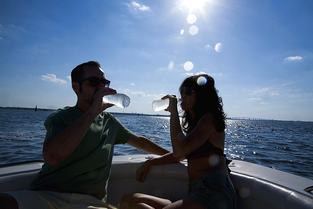 A couple out on their boat drinking bottled water