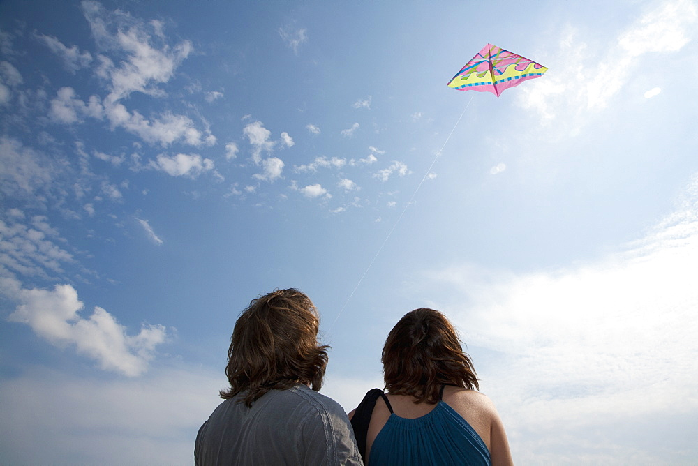 A young couple flying a kite, rear view