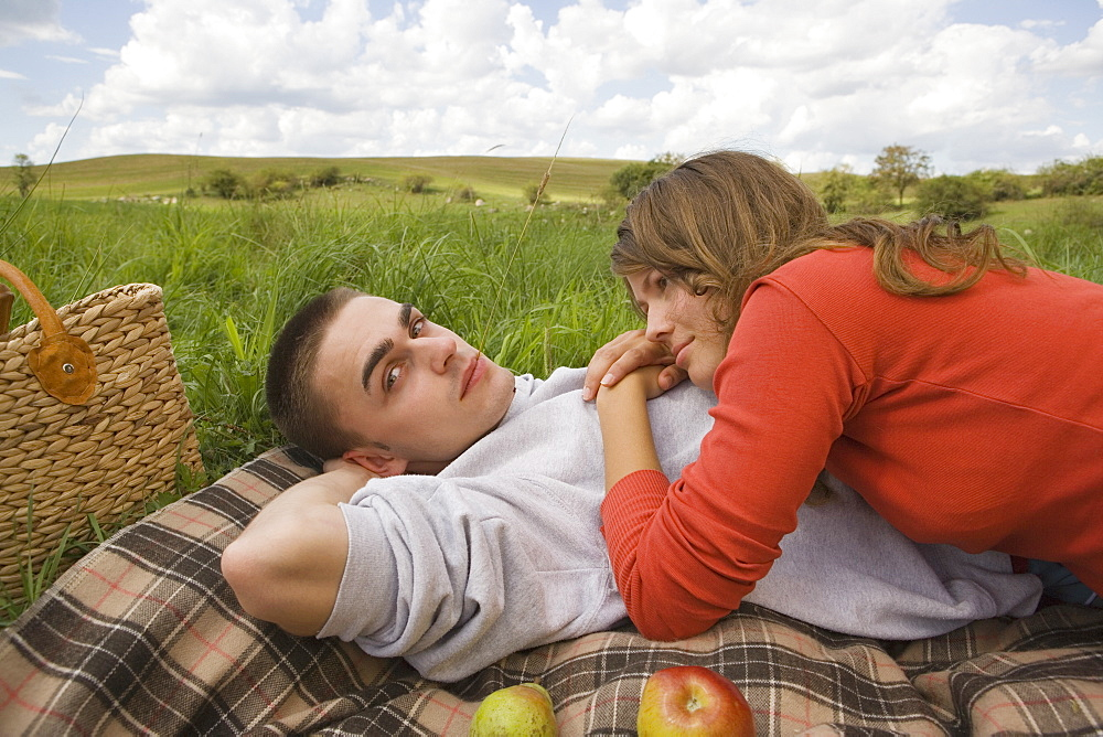 Young couple lying together on picnic blanket