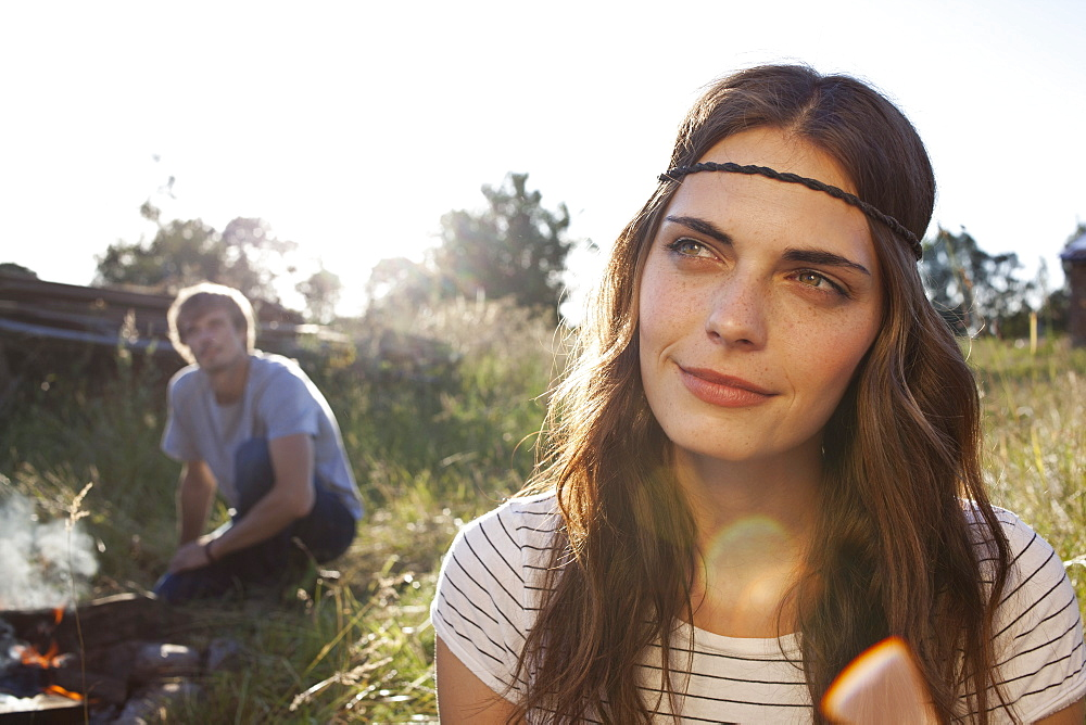 Profile of long haired girl in field, and guy in the background looking at her