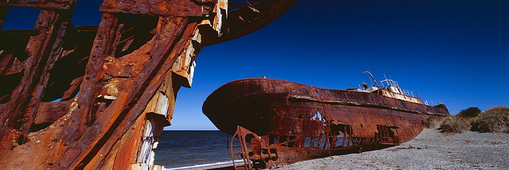 Panoramic view of abandoned shipwreck on shore at beach against blue sky, Patagonia