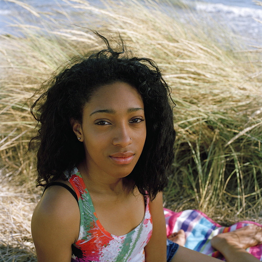 A teenage girl sitting on the beach, looking at camera