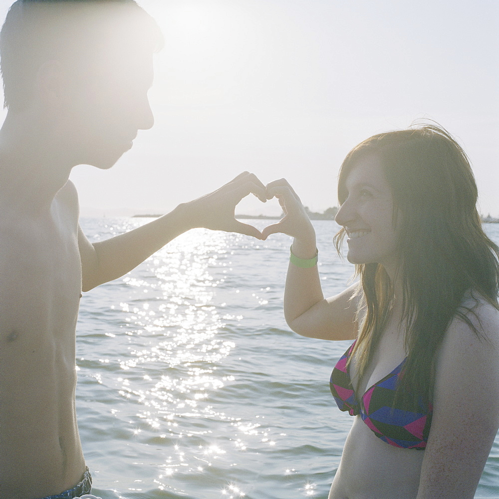 A young couple making a heart sign with their hands