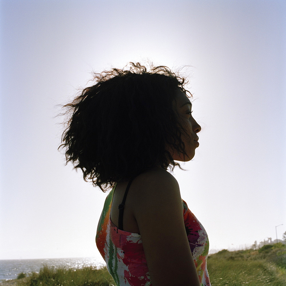 A teenage girl at the beach, staring at the view