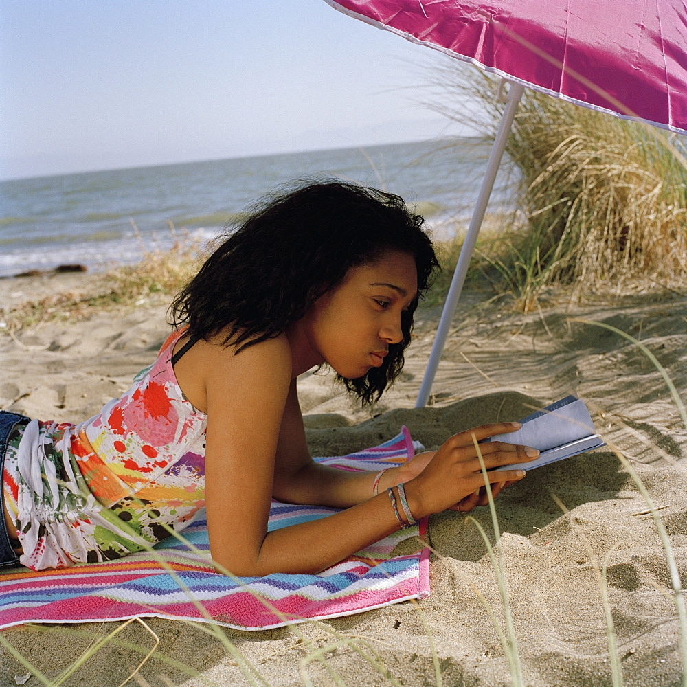 A teenage girl lying on the beach reading a book