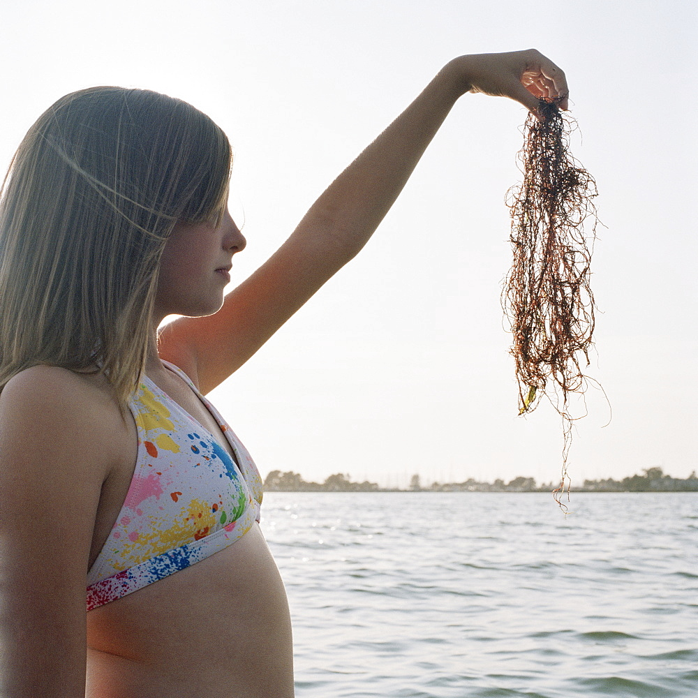 A teenage girl holding up seaweed