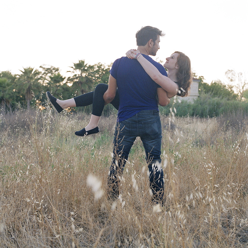 A young man carrying his girlfriend through a field