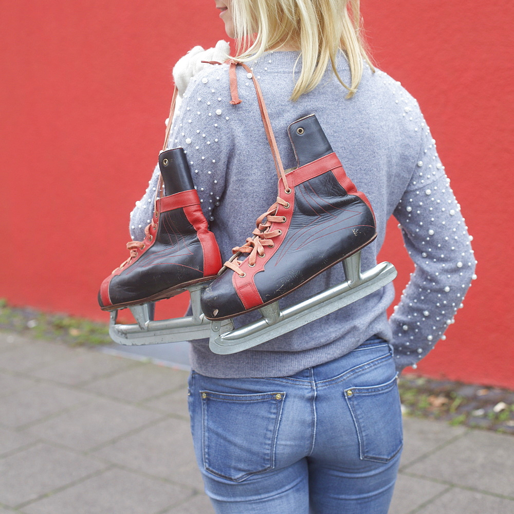 Woman carrying ice skates over shoulder