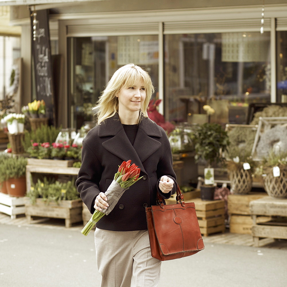 Woman carrying bunch of tulips on urban sidewalk