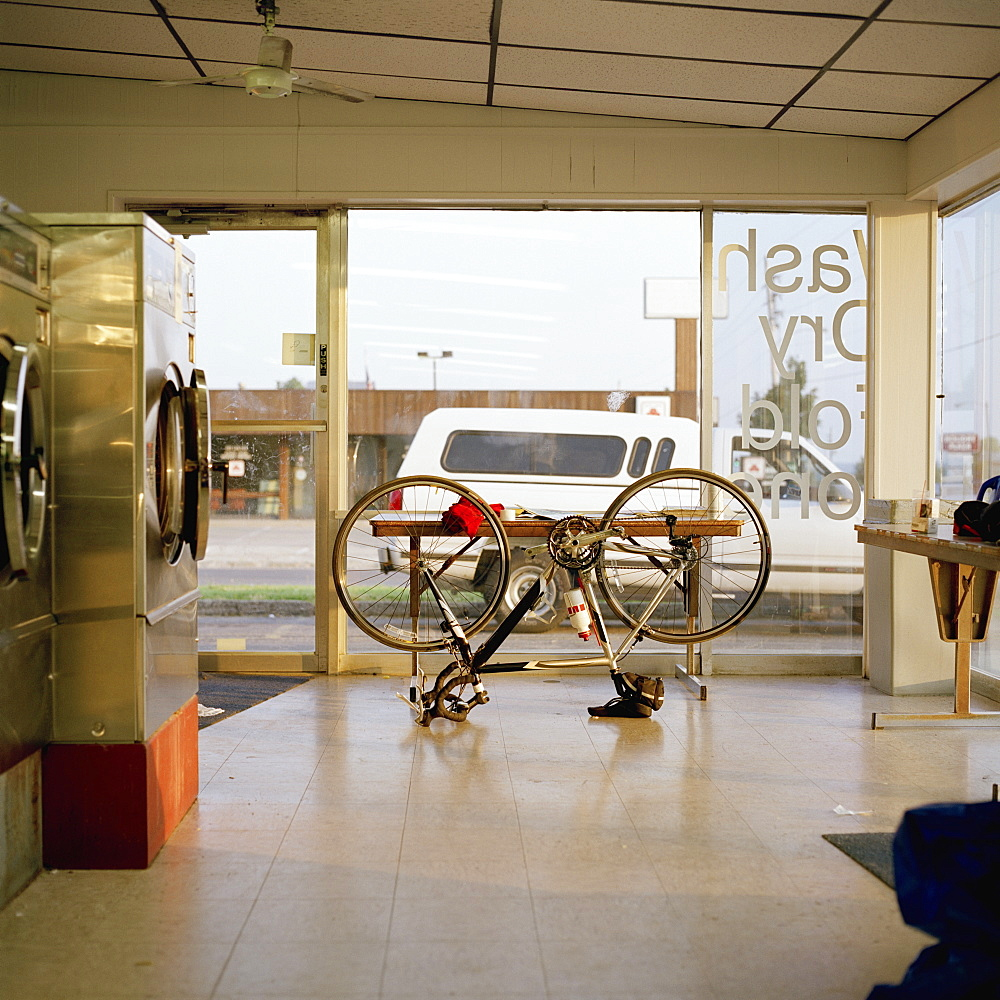 A bike upside down in a laundromat