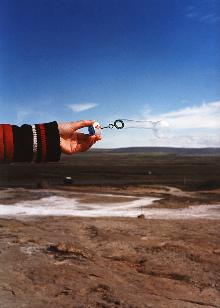 A hand holding a bubble dispenser with the ocean in the background