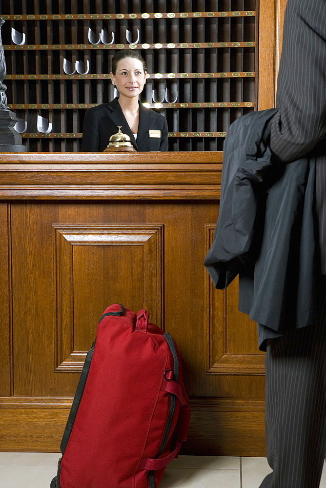 Hotel clerk serving businessman at hotel reception