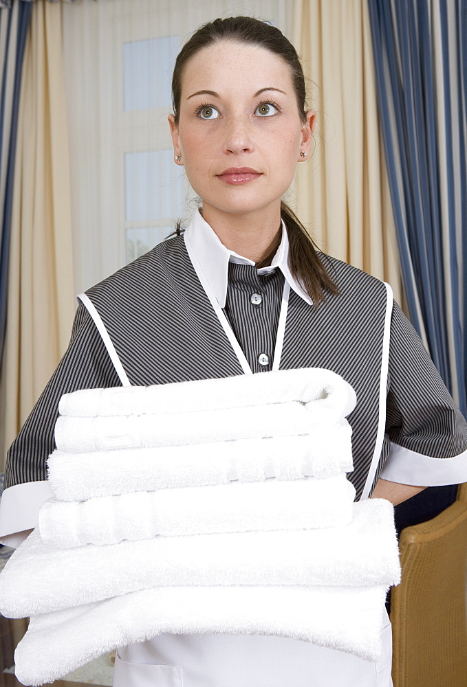 Uniformed maid holding stack of folded towels