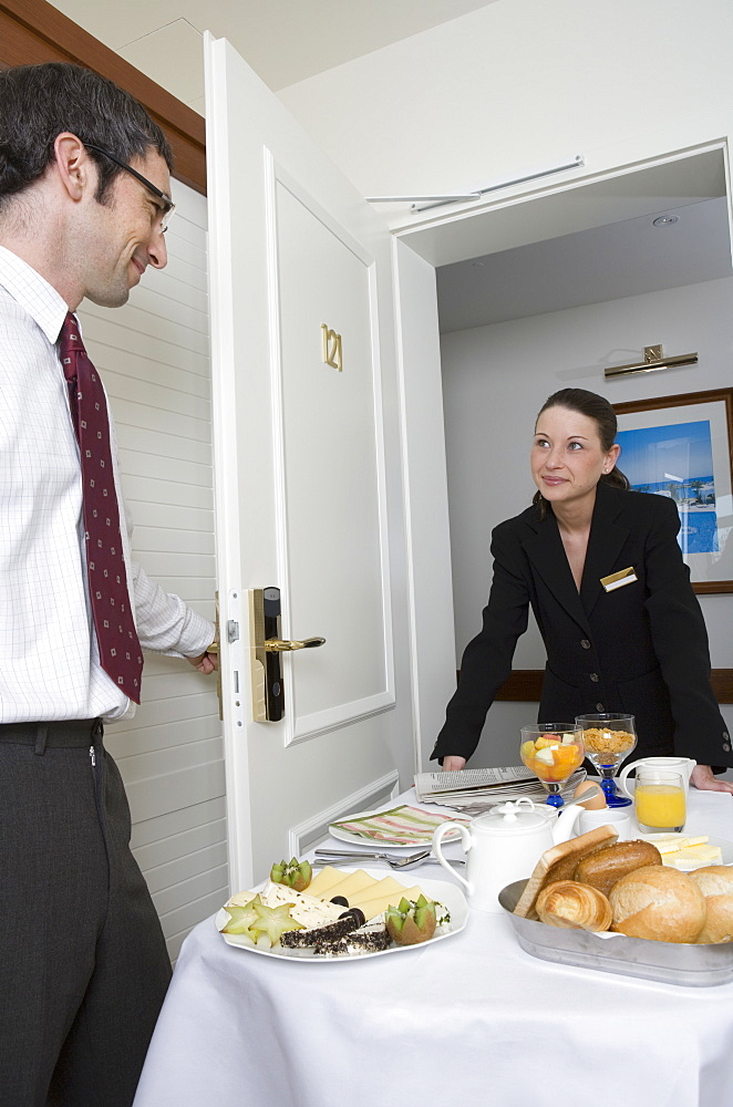 Woman delivering breakfast on push cart to businessman in hotel room