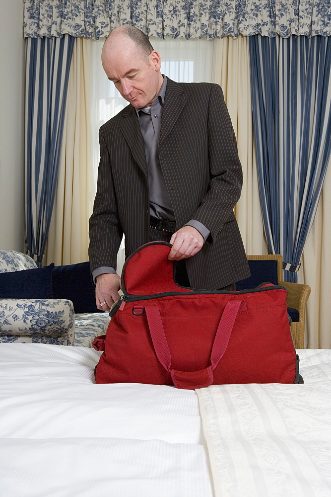 Businessman packing bag in hotel room