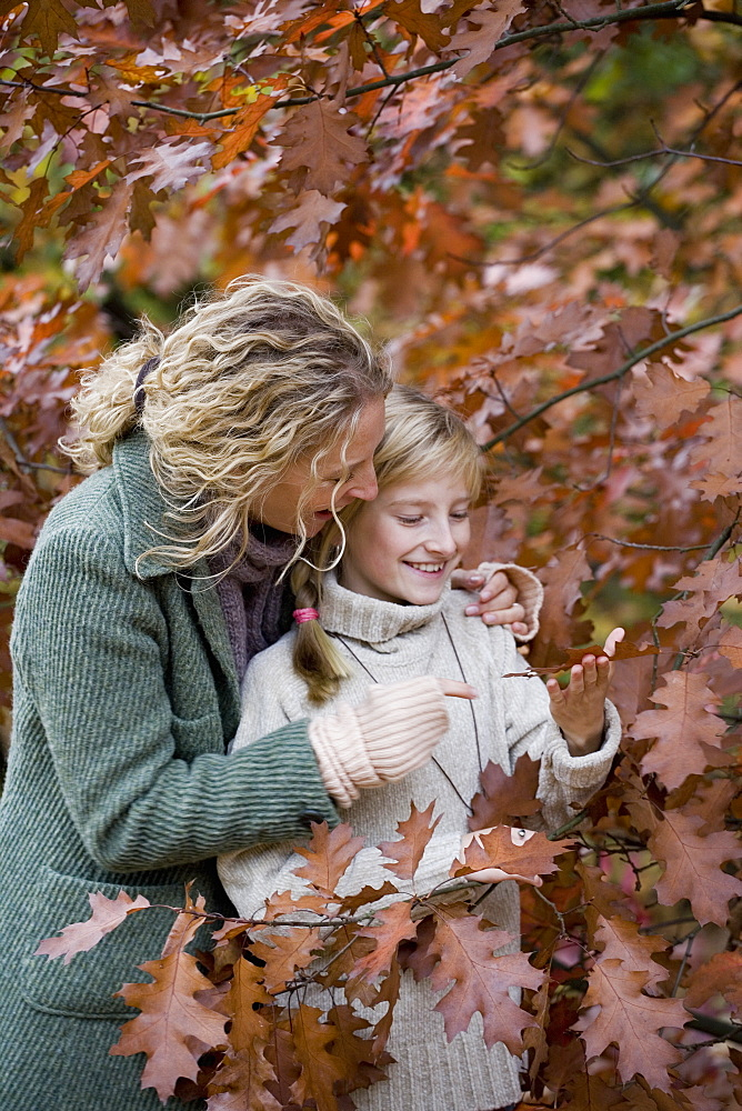 Mother and daughter standing amongst tree branches with autumn leaves