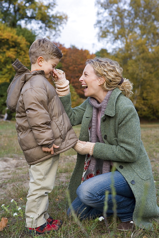 Mother pinching son's nose in park whilst zipper up parka