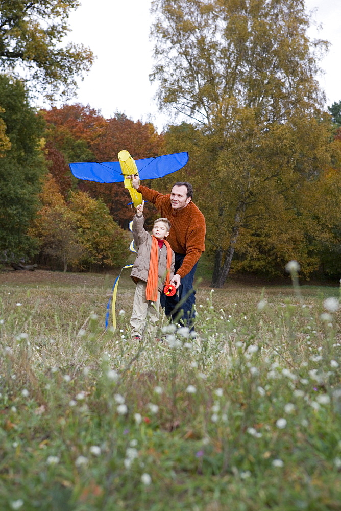 Father and son launching a kite together in a park