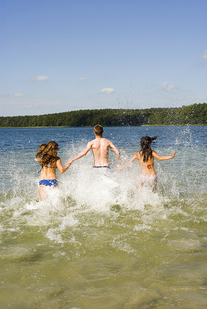 Group of friends running into lake