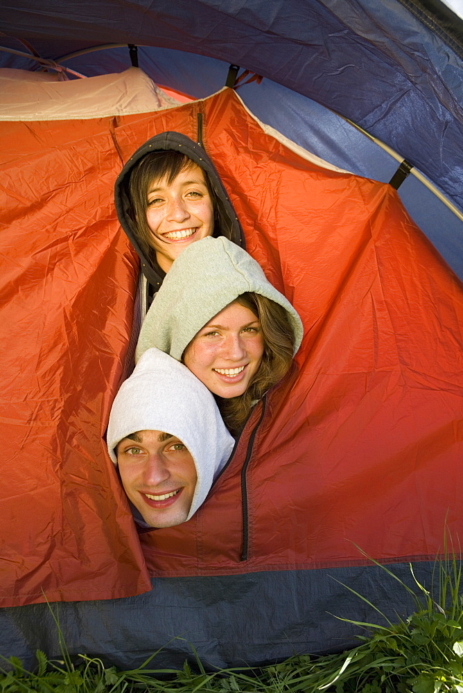Three friends crowded inside tent