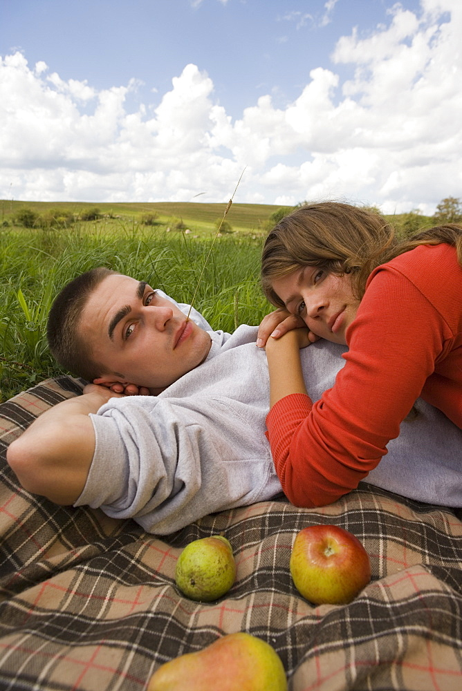 Young couple lying on blanket on grass