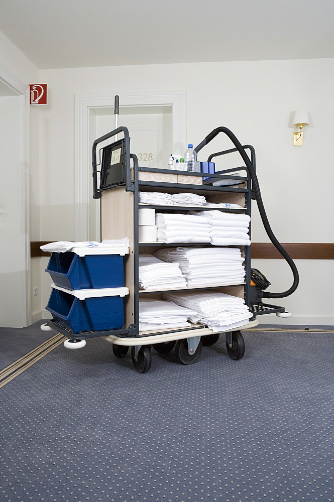 Trolley with room supplies and cleaning equipment in hotel corridor