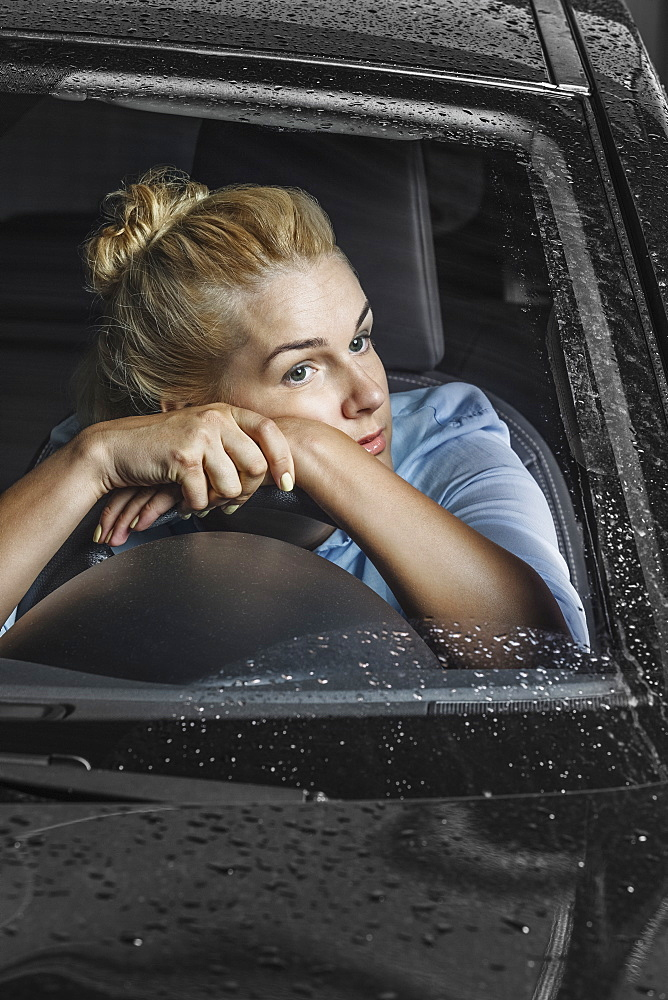 Bored woman looking away while leaning on steering wheel in car