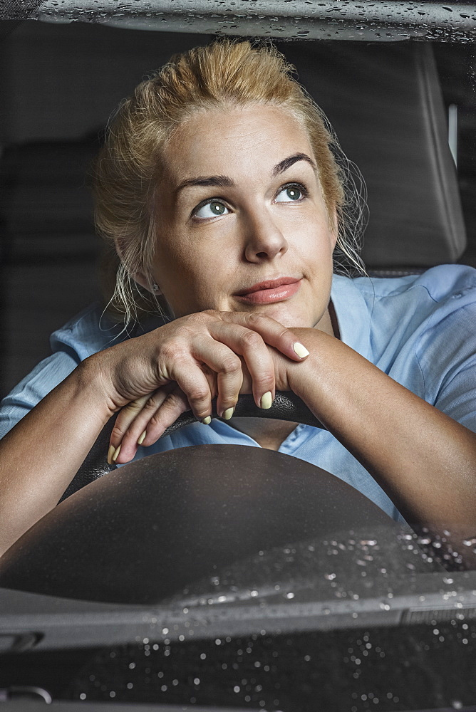 Thoughtful woman leaning on steering wheel in car