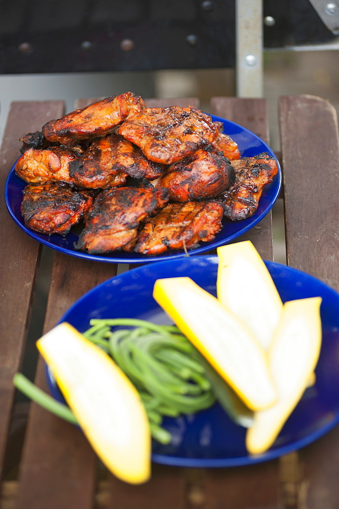 Grilled chicken and cucumber slices served on wooden table outdoors