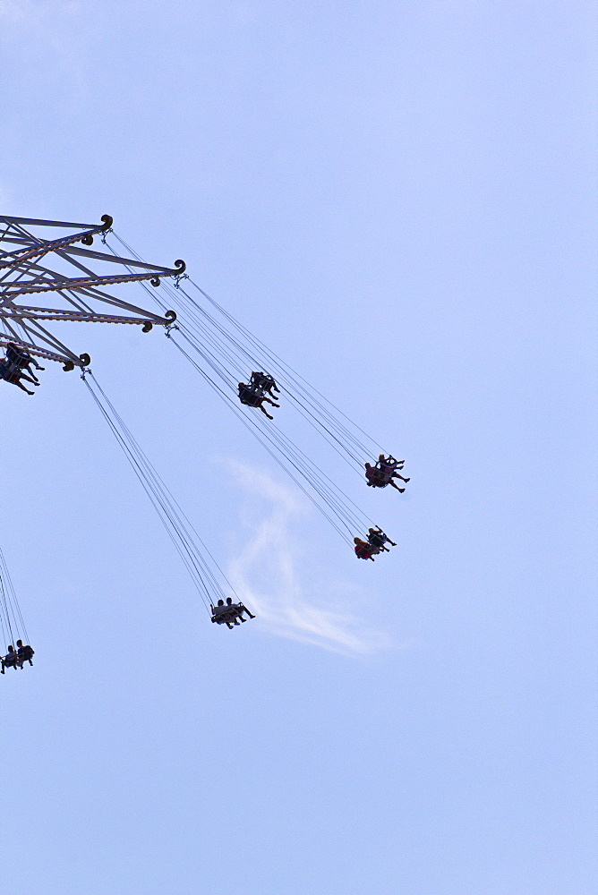 Low angle view of people enjoying on chain swing ride against blue sky