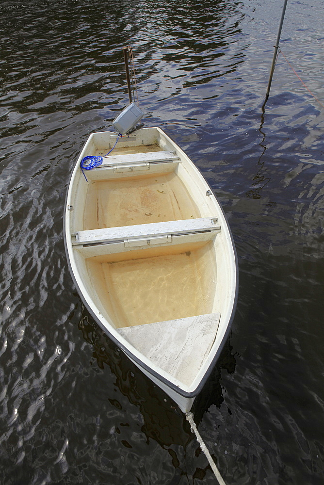 Boat filled with water moored in lake