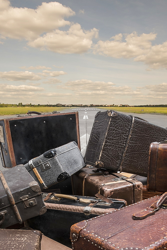 Old suitcases on street against sky
